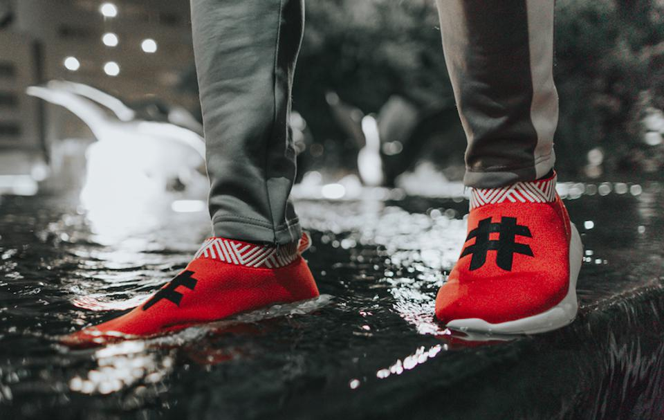 Red slip-on sneakers topped with hashtag logo, walking through a fountain