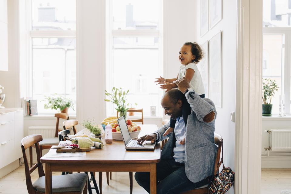 Father carrying cheerful daughter on shoulder while working on laptop at table in house