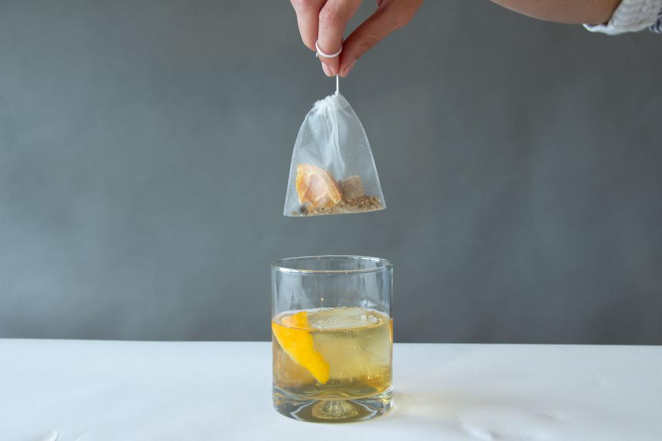 Teabag containing dehydrated infusions, above a cocktail glass.