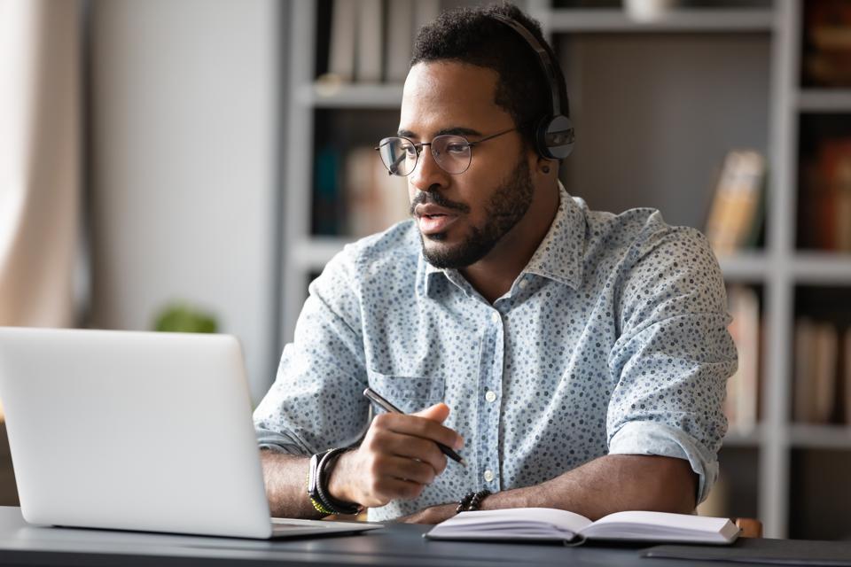 Man watching webinar on laptop and taking notes.