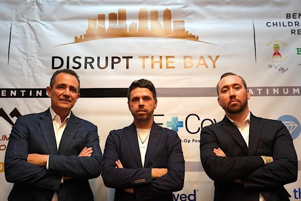 Three men standing in front of a Disrupt the Bay banner.