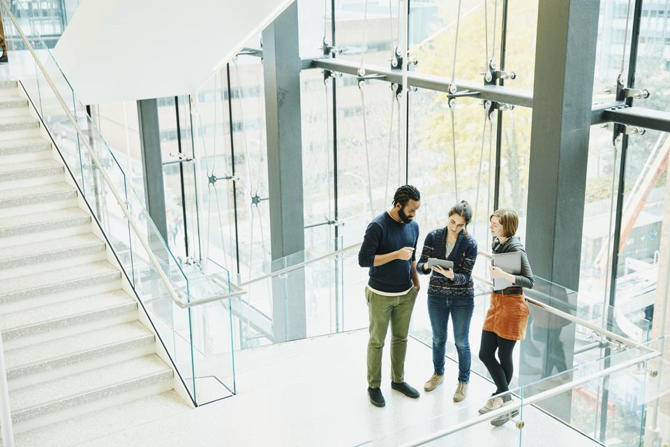 Coworkers discussing project on digital tablet on stairs of office building