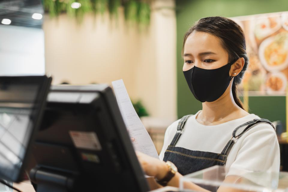 A restaurant worker wearing a protective face mask reviews an order at their point of sale