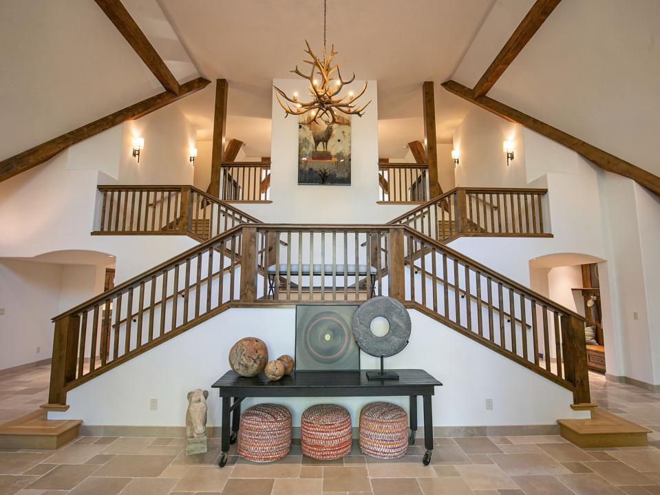 A wooden staircase features deer antlers and an image of wildlife with elegant lighting.