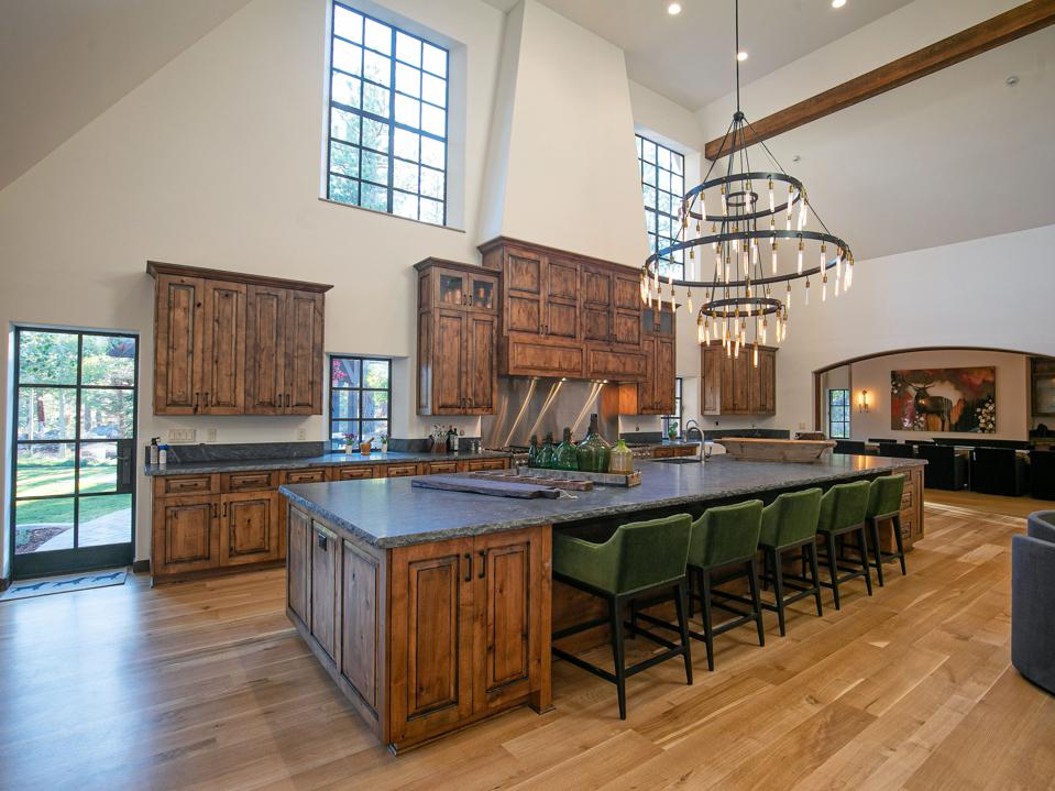 Main kitchen with a large dining island and chairs with a massive light fixture overhead