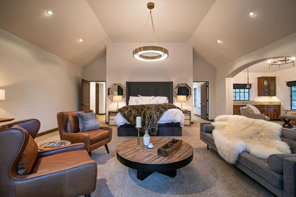 A bedroom has a seating area with a round table and a sofa and two leather chairs