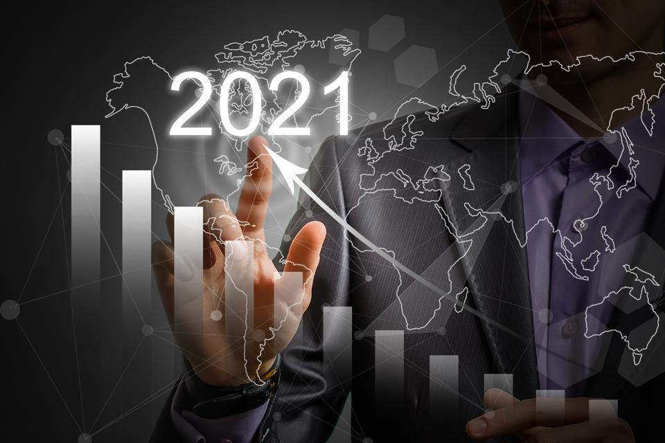 Man's hand pointing graph of success in 2021 year. Growing business concept
