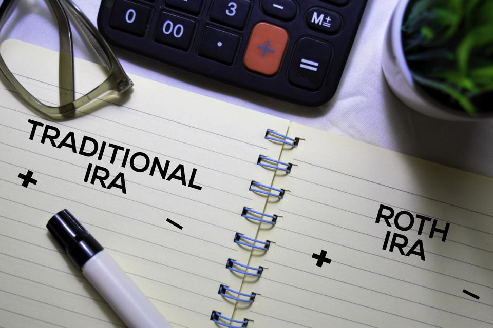 Traditional IRA and Roth IRA text on a book isolated on office desk.