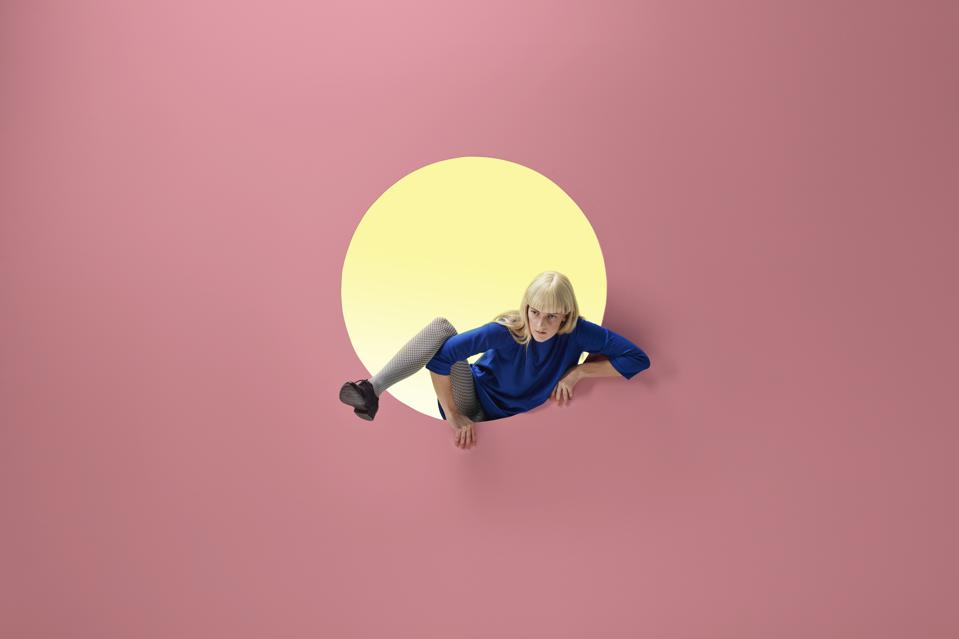 Woman crawling out of round opening in wall symbolizes struggle to come up with new ideas