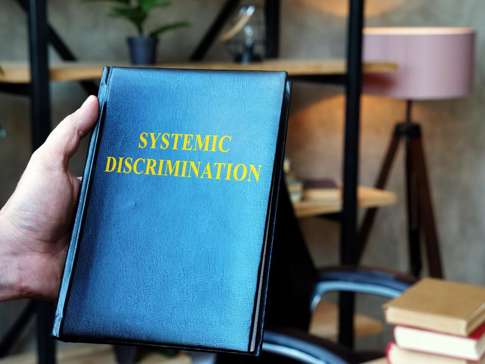 Hand holding book about Systemic Discrimination in the office.