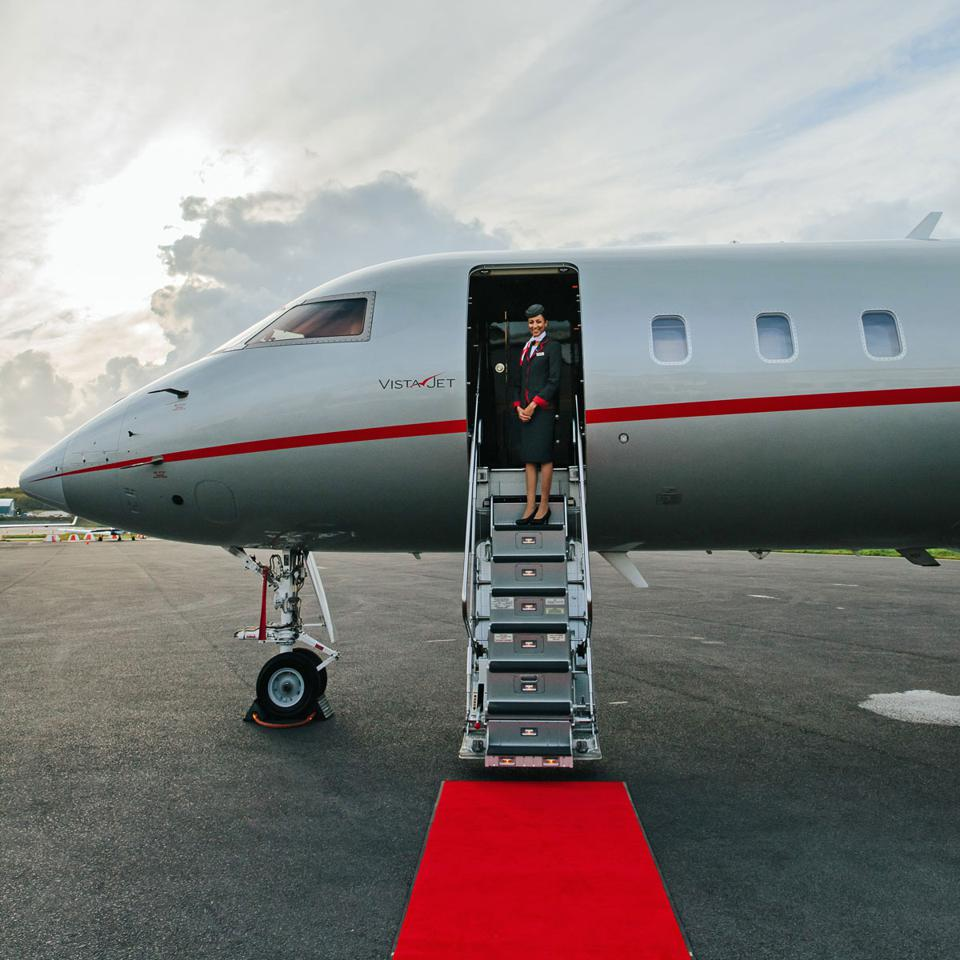 A stewardess welcoming onboard a VistaJet private aircraft