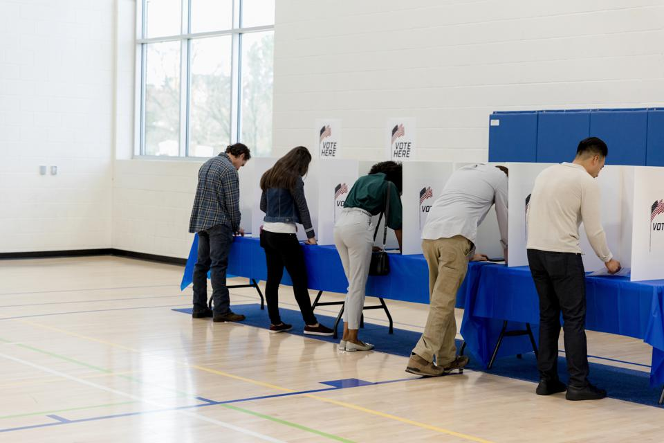 People stand at voting booths along the gym wall