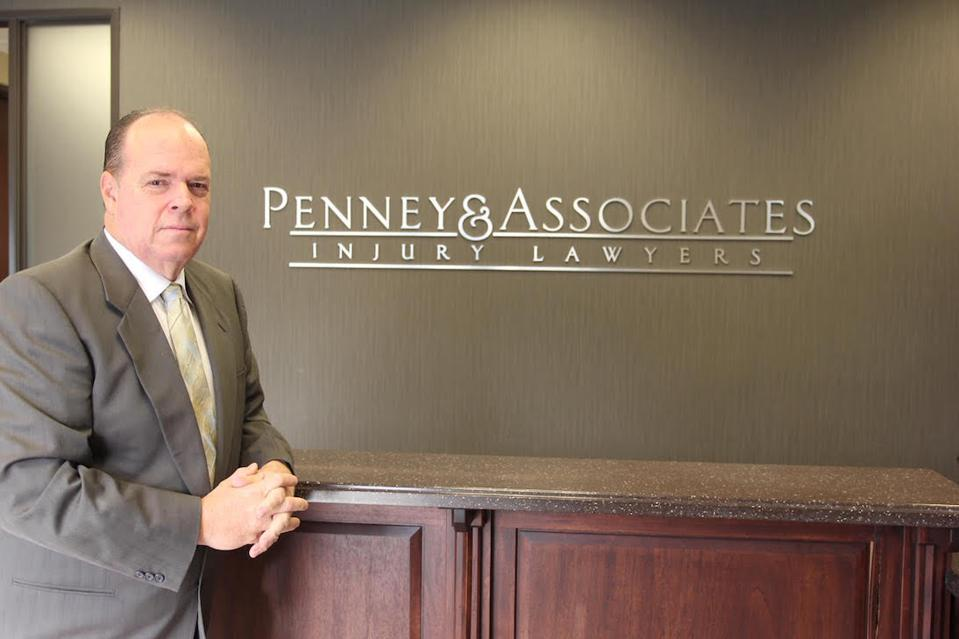 Middle-aged man in a suit in front of a Penney & Associates Injury Lawyers logo