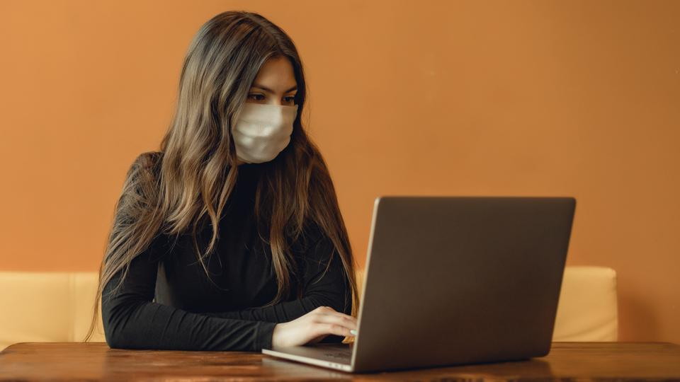 Portrait of adult woman with medical face mask  on yellow background. Concept with copy space. She is working with modern gray laptop