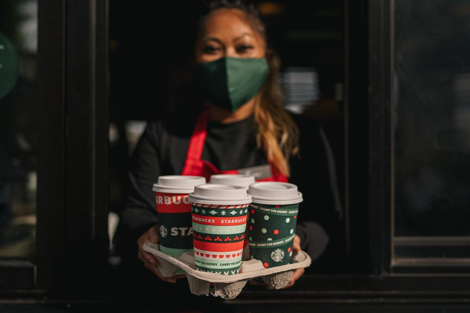 Starbucks barista in mask holding holiday coffee cups
