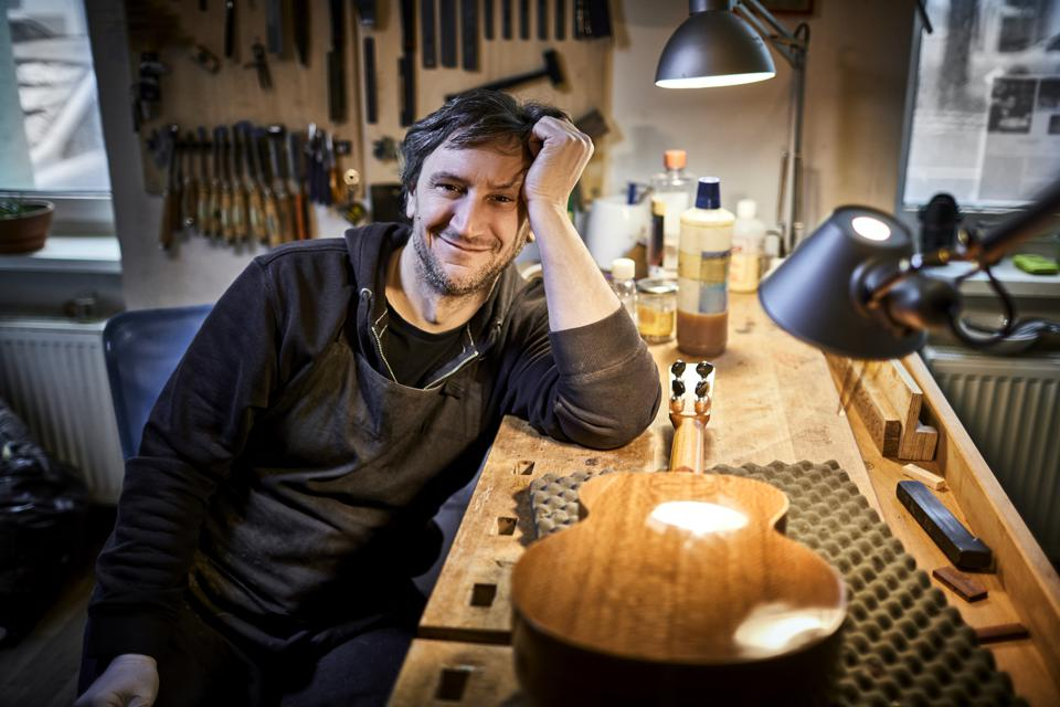 Portrait of smiling instrument maker sitting in his workshop