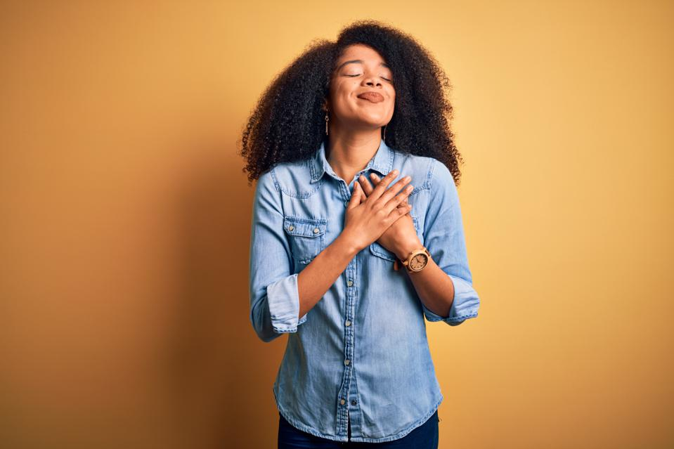 Young woman with hands on chest with closed eyes and grateful gesture on face.