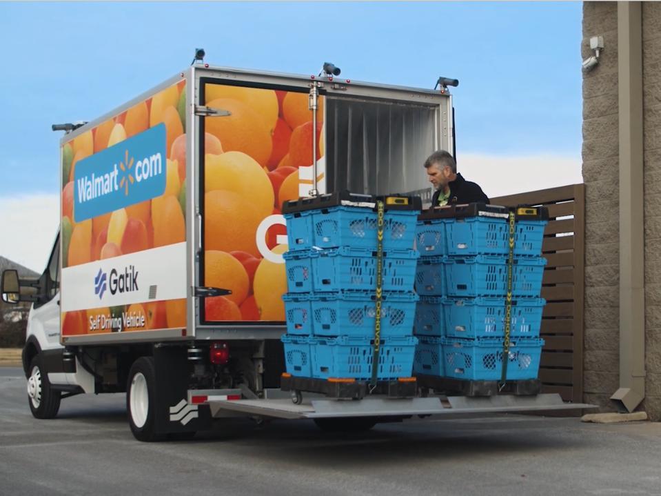 A worker loads crates onto a Gatik self-driving vehicle with a Walmart logo.