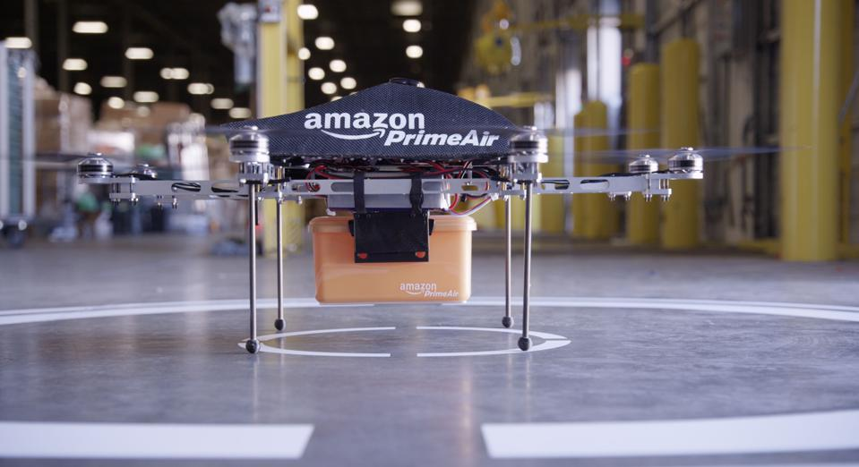 Amazon Prime Air delivery drone with a package, parked on a warehouse floor with the blades splinning