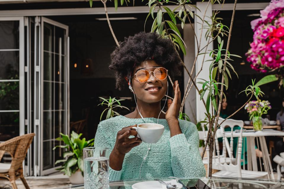 Hip black chick with rose colored glasses smiling, sipping coffee, living her best life