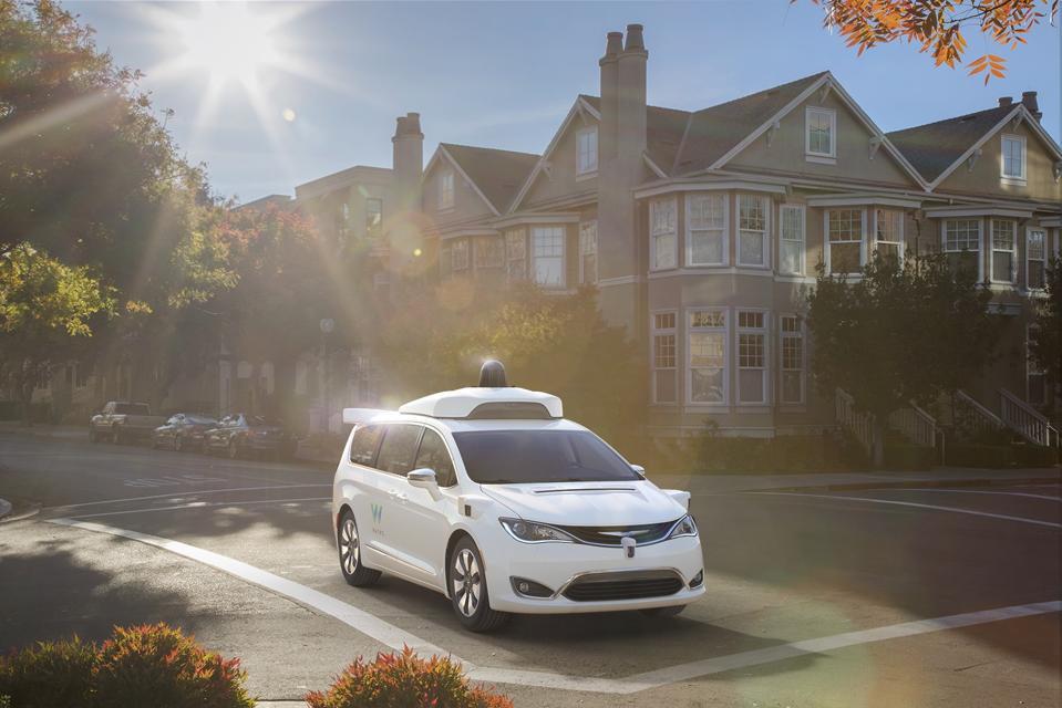Waymo self-driving minivan proceeds through a residential intersection