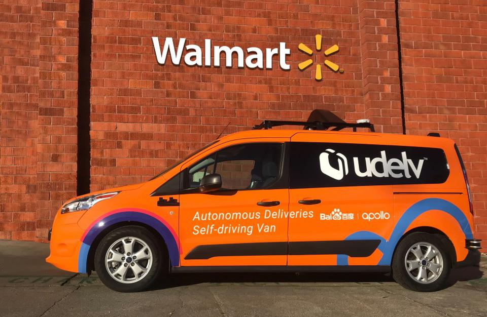 A UDelv autonomous delivery van in front of a brick wall with a Walmart logo