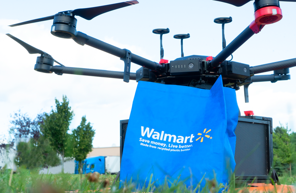 A Flytrex drone sitting in a field, next to a Walmart shopping bag