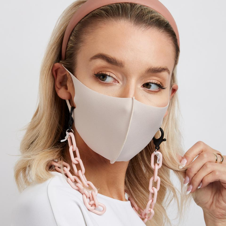 A white woman with blonde hair models a grey face mask with the ai pink beige mask chain.