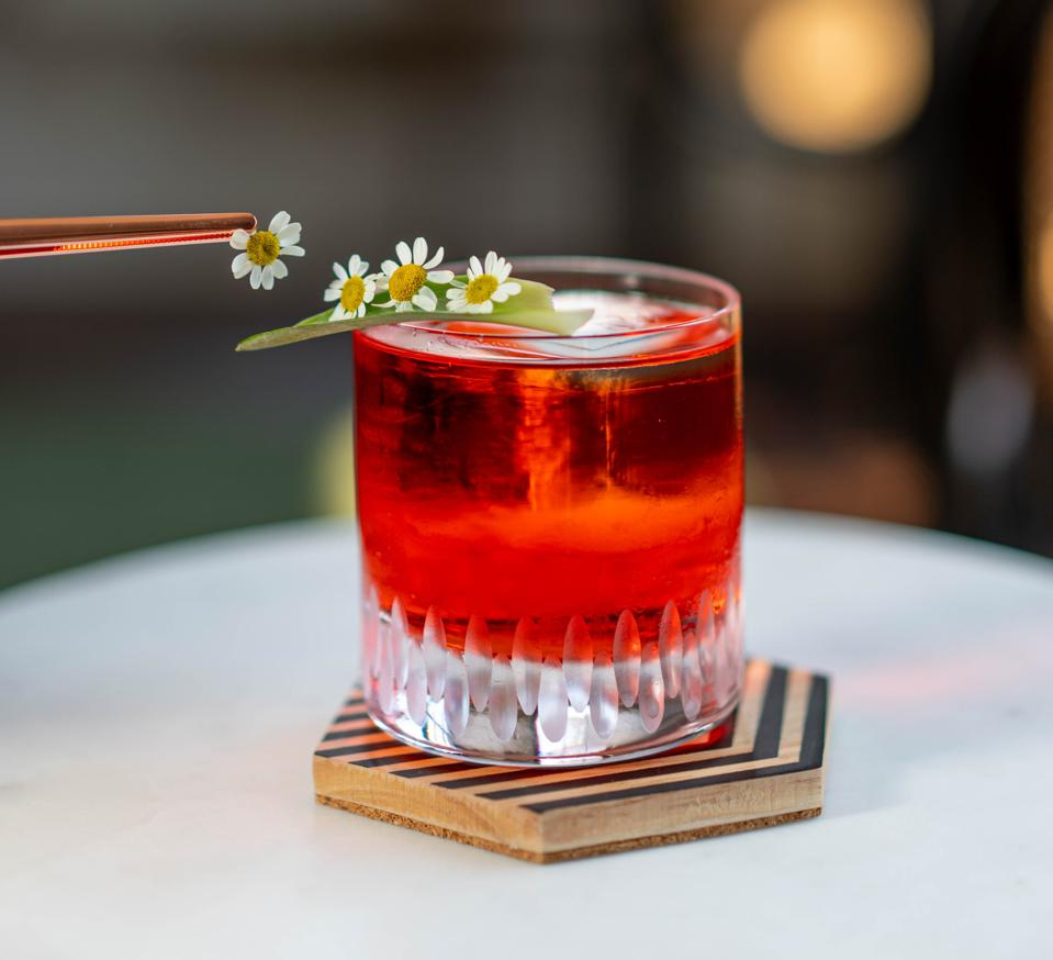 a cocktail getting garnished with a flower