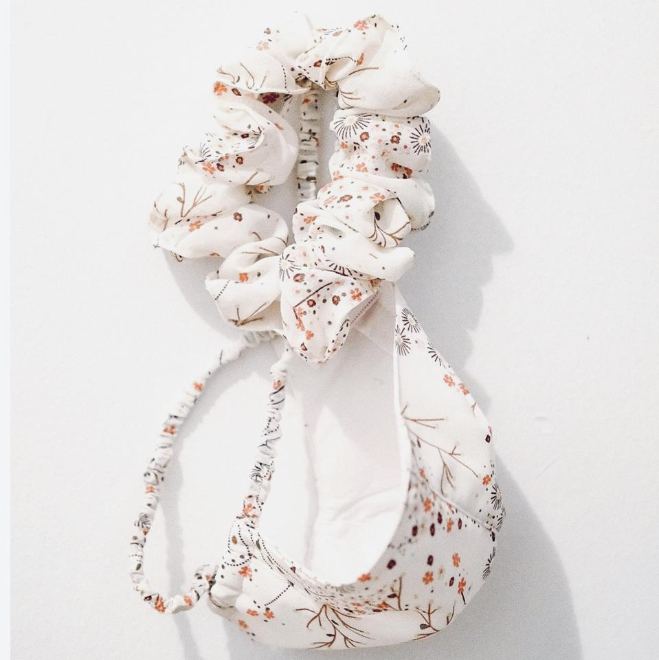 A white floral patterned mask hangs against a white wall with a matching scrunchie.