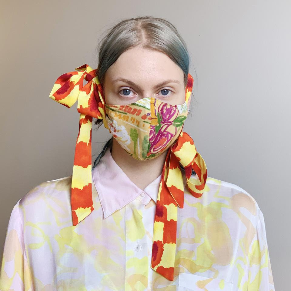 A white woman with white and blue hair poses in a yellow and orange face mask with bows.