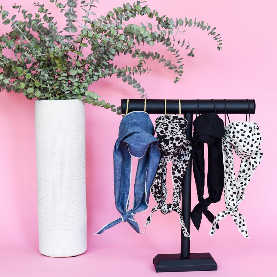 Four mask scarves displayed on a black stand next to a plant against a pink backdrop.