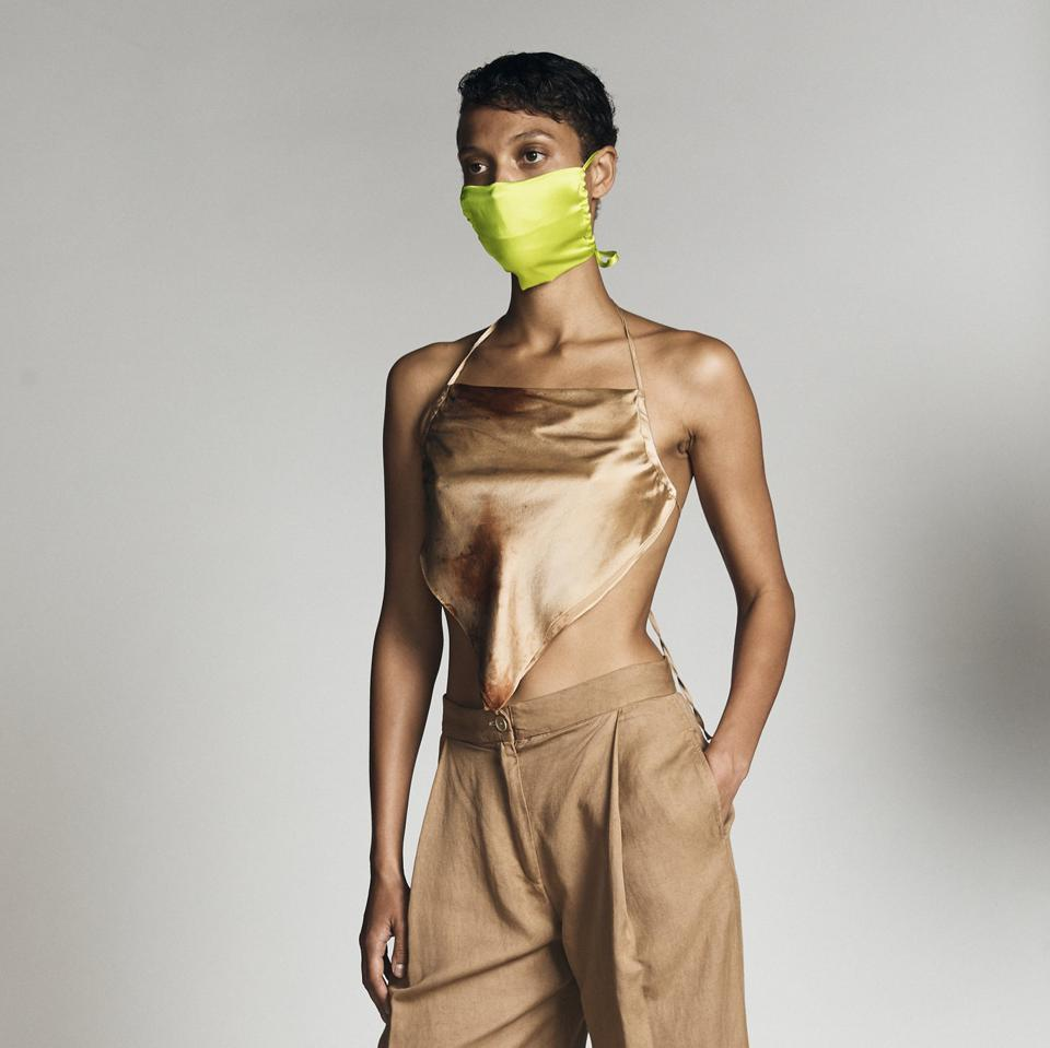 A Black woman models against a white backdrop wearing a neon green mask and camel silk top
