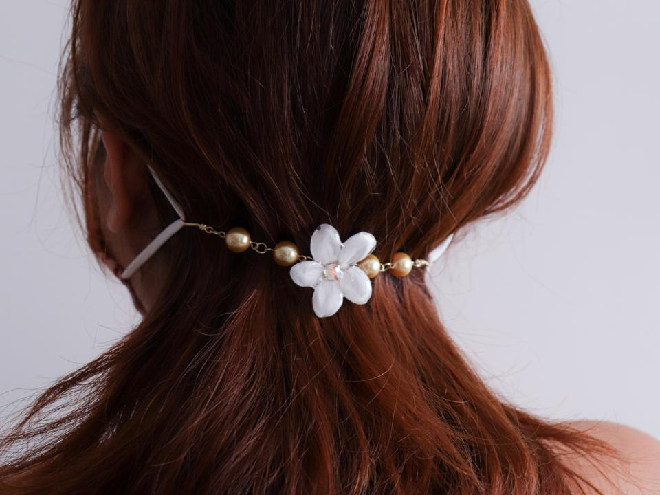 A floral mask accessory holds ear straps in place against reddish brown hair.