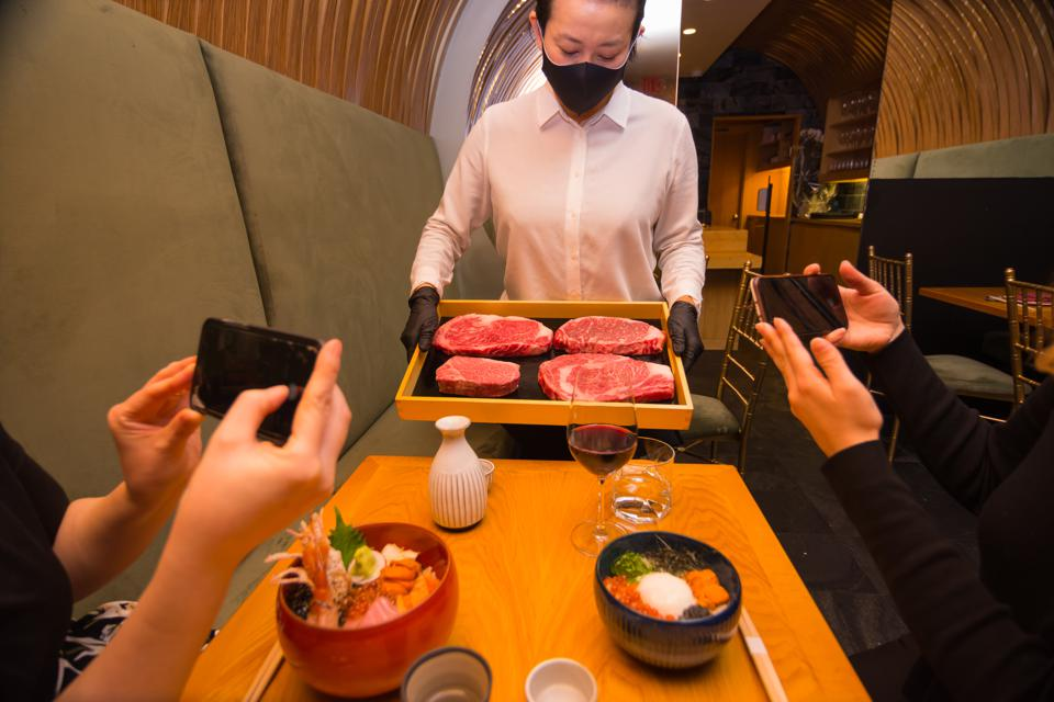 server at j-spec holding different wagyu steaks to diners with phones