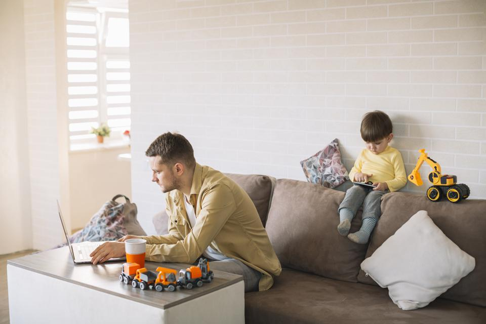 Man working from home with toddler on back of sofa, and toys on coffee table