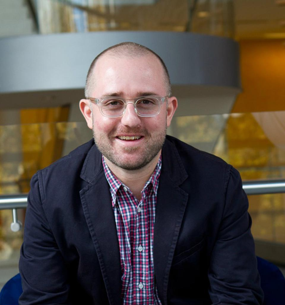 Young caucasian man, bald, with clear glasses, wearing a dark blue suit and plaid shirt, looking at the camera