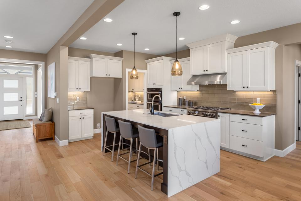 beautiful kitchen in new home with island, pendant lights, and hardwood floors.