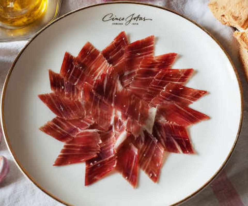 A plate of thinly sliced, marbled cured ham