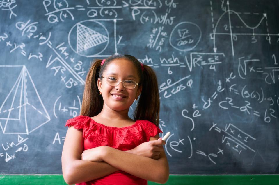 Portrait d'une jeune fille heureuse résolvant un problème mathématique complexe au tableau