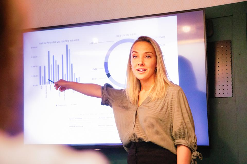 Young blond female manager explaining quarterly results on large led screen
