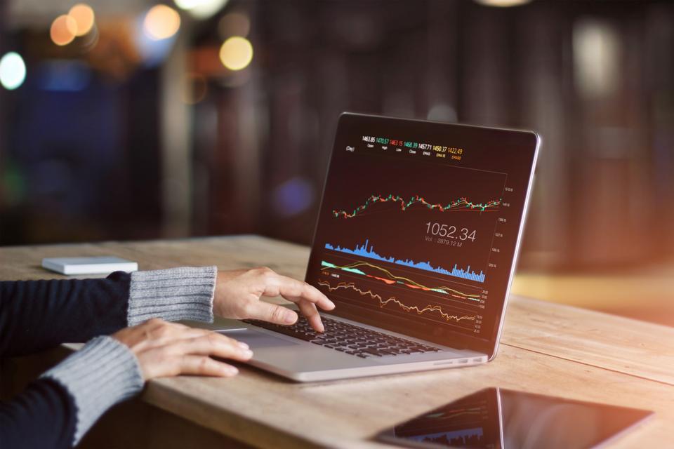 Businessman using laptop for analyzing stock exchange