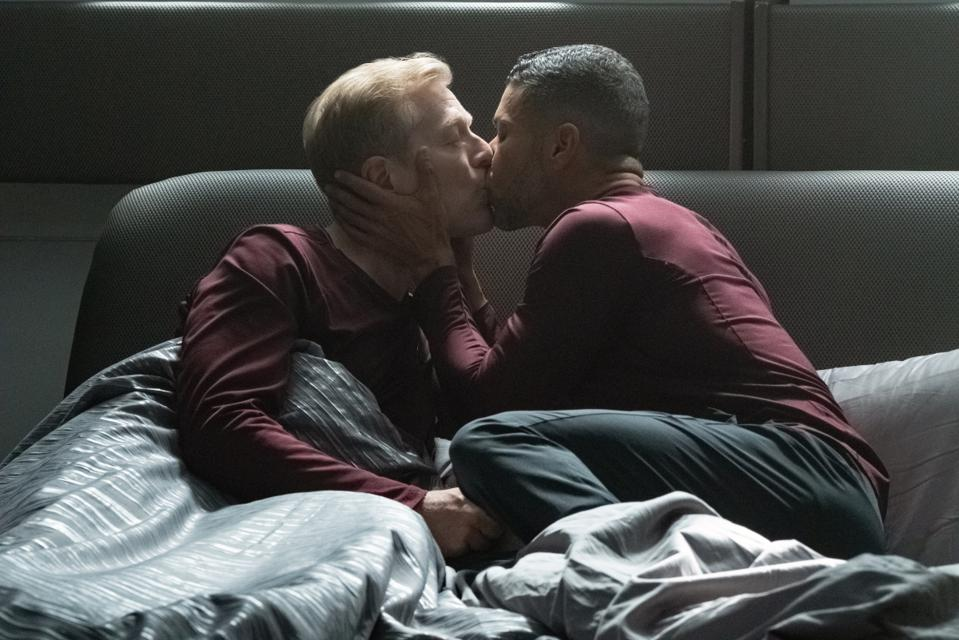 Lt. Commander Paul Stamets is kissed by his partner, Dr. Hugh Culber in their bed aboard the U.S.S. Discovery.