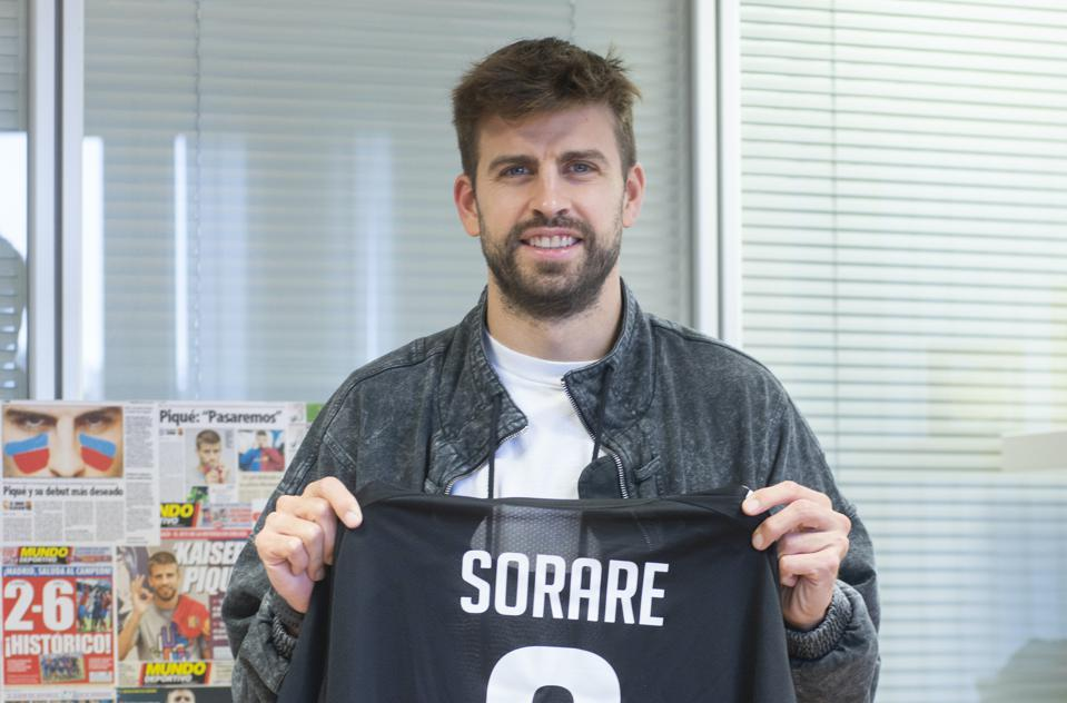 Gerard Pique holds up a black Sorare shirt after becoming their new strategic advisor.
