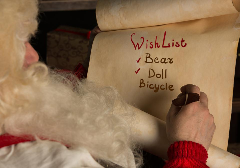 Santa Claus sitting at home and writing on paper roll
