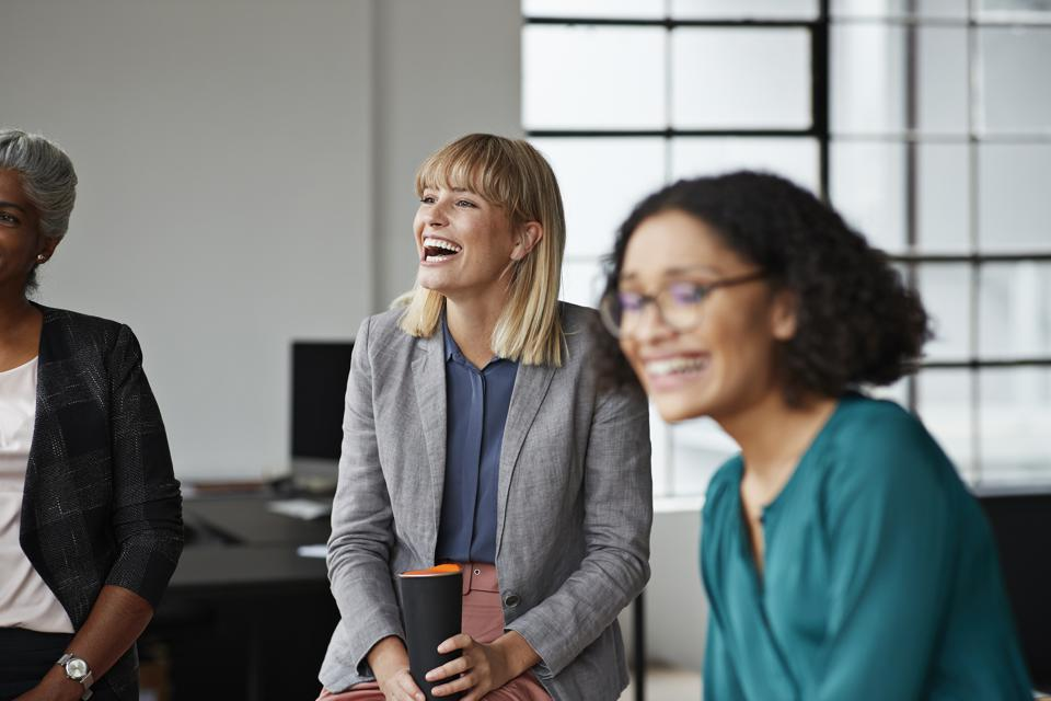 Excited businesswoman looking away in office