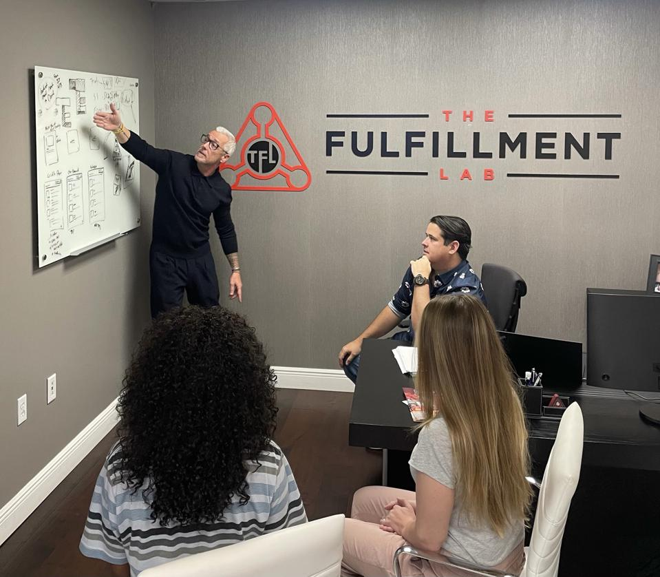 four people in an  office looking at a  whiteboard