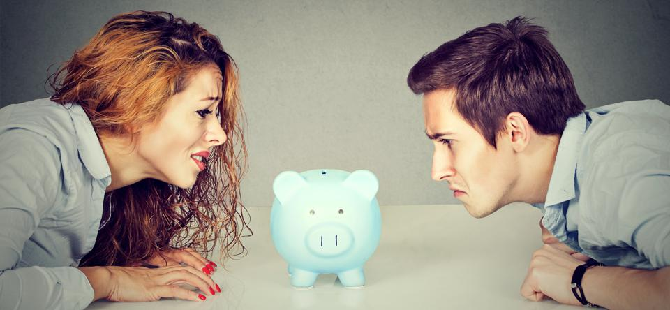 A divorcing couple stare angrily at a piggy bank.