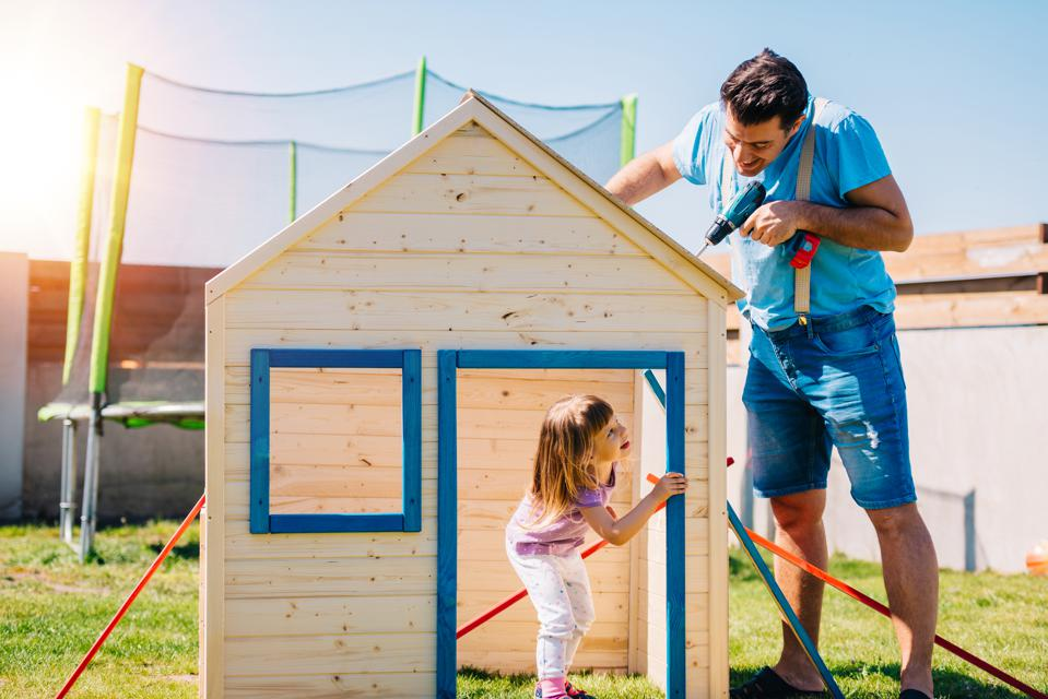 Father and daughter building a wooden house together