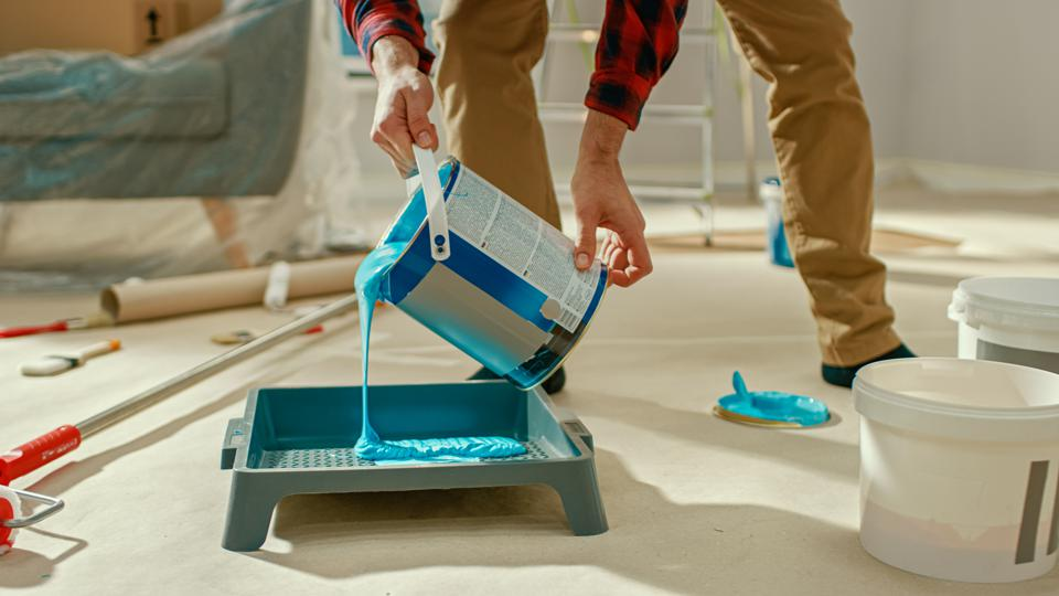 Young Man in Brown Jeans and Red Checked Shirt Picks Up a Can of Light Blue Paint and Pours it Into a Tray. Room Renovations at Home.
